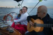 Couple laughing on board a boat while man plays the guitar at sunset