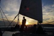 Man playing saxophone at sunset on a catamaran
