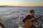 Man playing guitar on the back of a yacht at sunset in Barcelona